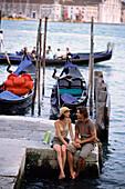 Caucasian sitting together by canal, Venice, Veneto, Italy, Venice, Veneto, Italy