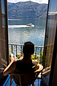 Woman overlooking rural lake from balcony, Lugano, Ticino, Switzerland, Lugano, Ticino, Switzerland