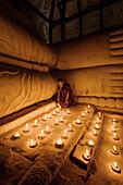 Asian monk lighting candles in temple, Bagan, Mandalay, Myanmar