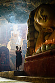 Asian monk lighting incense in temple, Hpa-An, Kayin, Myanmar
