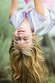 Caucasian girl hanging upside down outdoors, Santa Fe, New Mexico, USA