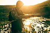 Mari man fishing in lake, C1