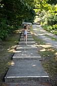 Caucasian children climbing stairs near rural path, C1