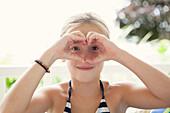 Caucasian girl making heart shape around eyes, C1