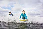 Boys surfing together in waves, C1