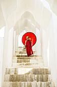 Asian Buddhist monk carrying umbrella on staircase at Hsinbyume Pagoda, Mandalay, Sagaing, Myanmar, C1