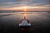 Caucasian man in deck chair overlooking sunset on beach, C1
