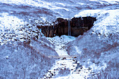 Waterfall and river in snowy landscape, Svartifoss, Sudhurland, Iceland, C1