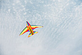 Colorful airplane kite flying in blue sky, C1