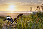 Laptop on deck chair overlooking sunset on beach, C1
