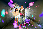 Caucasian couple carrying boom box and throwing confetti in tunnel, Seattle, Washington, United States