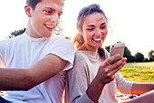 Caucasian couple using cell phone outdoors, Seattle, Washington, United States