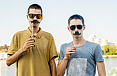 Caucasian men playing with fake mustaches in city, Yekaterinburg, Ural, Russia