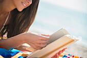 Caucasian woman reading book on beach, Jupiter, Florida, USA