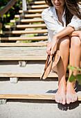 Caucasian woman with sandy feet sitting on beach staircase, Jupiter, Florida, USA