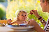 Caucasian mother feeding baby son at table, Santa Fe, New Mexico, USA