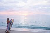 Caucasian surfer holding paddleboard on beach, Miami Beach, Florida, United States