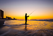 Blurred view of silhouette of man fishing in waves on beach at sunset, Coast, New York, USA