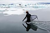 Caucasian surfer carrying board in glacial water, Jokulsarlon, Iceland, Iceland