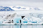 Caucasian surfer carrying board near glacial water, Jokulsarlon, Iceland, Iceland