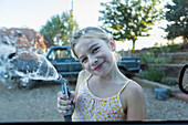 Caucasian girl spraying water from hose outdoors, Santa Fe, NewMexico, USA