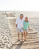 Caucasian couple walking on wooden boardwalk on beach, Santa Monica, California, USA
