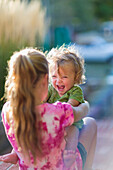 Caucasian sister holding laughing baby brother outdoors, Santa Fe, New Mexico, USA