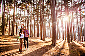Couple holding hands under trees in sunny forest, San Francisco, California, United States