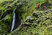 Caucasian hiker admiring waterfall and rock formations on mountainside, Southern Highlands, Iceland, ICELAND