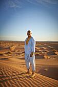 Guide smiling on sand dunes in desert landscape, Sahara Desert, Morocco, Morocco