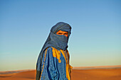 Guide wearing face protection in desert landscape, Sahara Desert, Morocco, Morocco