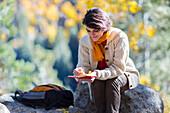 Mixed race woman reading journal on rock, Santa Fe, New Mexico, USA
