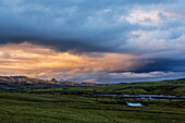 Clouds over green fields in rural landscape, Southern Highlands, Iceland, Iceland