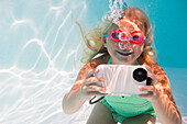 Caucasian girl taking photograph underwater in pool, Huntington Station, New York, USA
