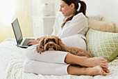 Caucasian woman using laptop with pet dog, Jersey City, New Jersey, USA