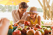 Mixed race mother and daughter browsing produce at farmers market, Virginia Beach, VA, USA