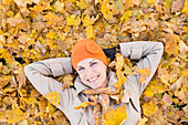 Older Caucasian woman smiling in autumn leaves, Provo, Utah, USA