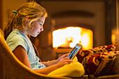 Caucasian girl using digital tablet in living room, Santa Fe, New Mexico, USA