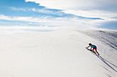 Caucasian girl climbing sand dune, White Sands, New Mexico, USA