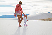 Caucasian mother and son walking on sand dune, White Sands, New Mexico, USA