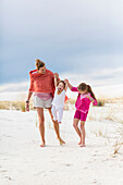 Caucasian mother and children walking on sand dune, White Sands, New Mexico, USA