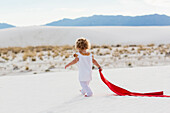 Caucasian boy playing with scarf on sand dune, White Sands, New Mexico, USA