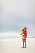 Caucasian mother holding son on sand dune, White Sands, New Mexico, USA