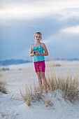 Caucasian girl standing on sand dune, White Sands, New Mexico, USA