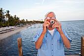 Caucasian man taking photographs on beach, Florida Keys, Florida, USA