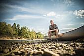 Older Caucasian man sitting in canoe on riverbed, Saint Louis, Missouri, USA