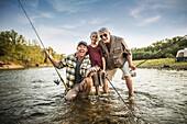 Three generations of Caucasian men fishing in river, Saint Louis, Missouri, USA
