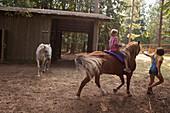 Caucasian children riding horse on farm, Hope, Idaho, USA