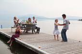 Caucasian family cheering as father and daughter dance on pier over lake, Hope, Idaho, USA