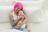 Caucasian mother with pink hair and tattoos cradling baby, Toronto, Ontario, Canada